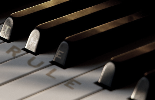 Photo of a piano, with The Rule written on it